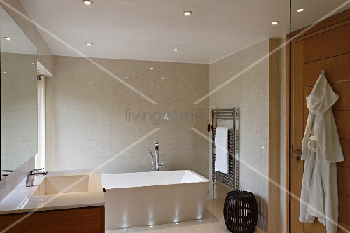 Bathtub lit by recessed floor lights against tiled wall and recessed spotlights in suspended ceiling in elegant modern bathroom