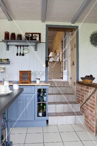 Blau-graue Küche im Landhausstil, mit Durchgang und Treppenstufen zum Wohnbereich