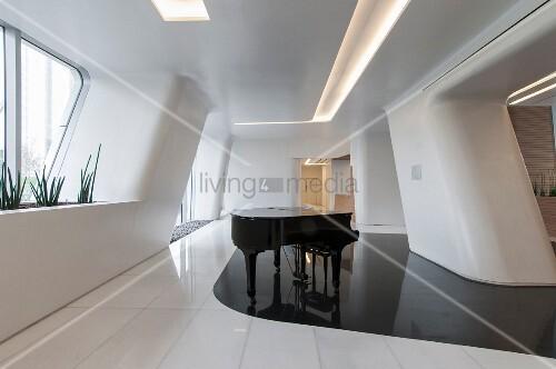 Grand piano on curved, glossy black floor area in futuristic white room