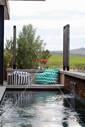 Small pool with water spout and comfortable beanbag on wooden terrace