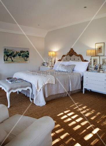 Bed with curved, upholstered headboard and antique-style bedroom bench; pattern of light and shadow on sisal carpet