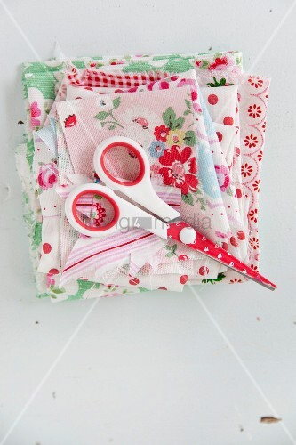Scissors on folded fabric with vintage patterns