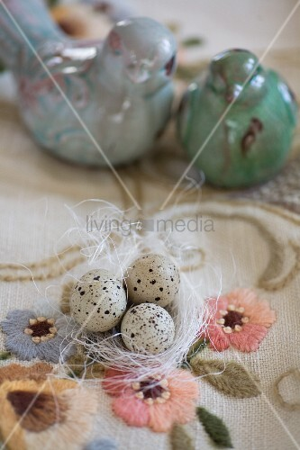 Quail eggs on white ornamental straw and turquoise bird ornaments on embroidered vintage tablecloth