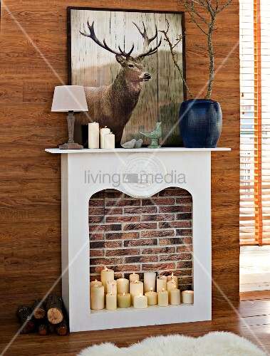Lit pillar candles in DIY faux fireplace