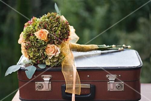 Festlicher Blumenstrauss aus apricotfarbenen Rosen und Hortensien mit Schleife, auf Vintage Koffer