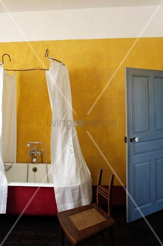 Vintage bathtub with shower curtain hanging from metal frame in rustic bathroom with yellow wall and blue door