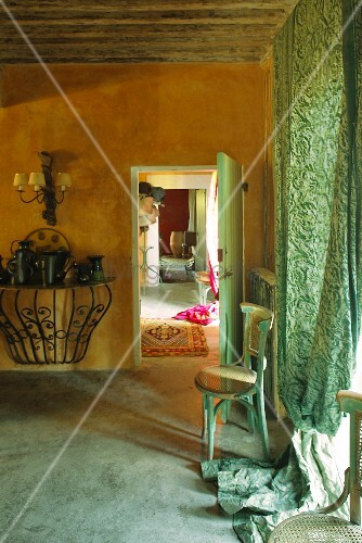 Ochre interior with green. floor-length curtains on window and wooden chair