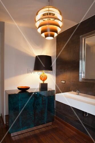 Table lamp on elegant sideboard, sink and retro pendant lamp in designer bathroom