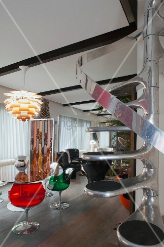 Retro seating area with colourful transparent plastic shell chairs below Artichoke lamp and space-saving newel staircase