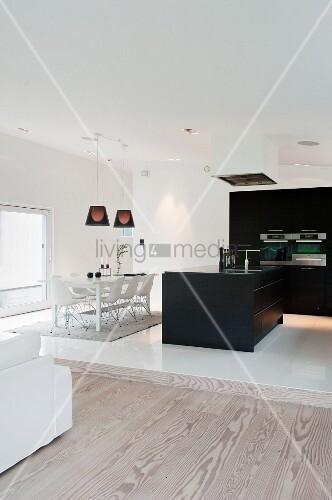 Blick auf weissen Essplatz und schwarze Küche in offenem Wohnraum