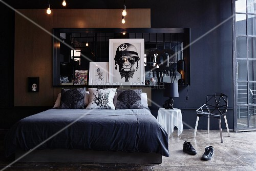 Dunkles Schlafzimmer mit Doppelbett vor Wand mit gerahmtem Spiegel ...
