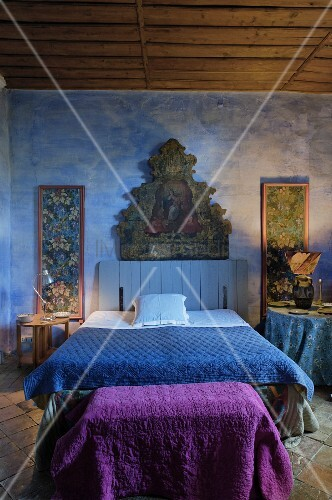 Rustic bedroom with religious painting on blue-painted wall, double bed with blue bedspread and purple blanket on trunk at foot of bed
