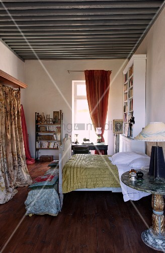 Quilt on antique sleigh bed and wardrobe with patterned curtain in Mediterranean interior