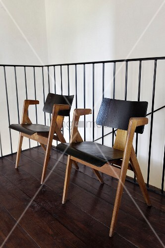 Retro chairs with pale wooden frames against metal landing balustrade