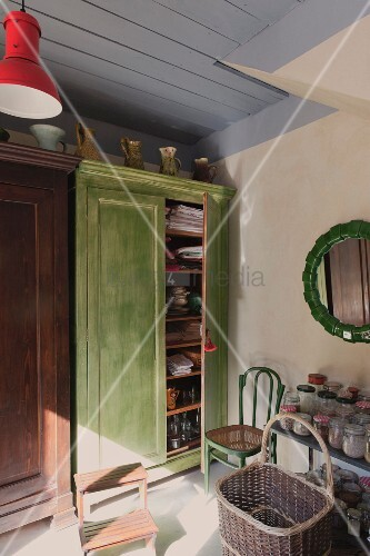Basket in front of storage jars on table next to green-painted wooden cupboard with open door