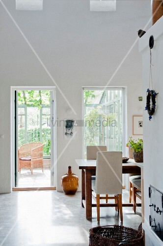 Bright dining area and open French windows leading to conservatory