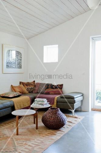 Übereck Lederliegen mit Decken und Kissen, Retro-Tische und bauchiger Flechtkorb auf Teppichläufer