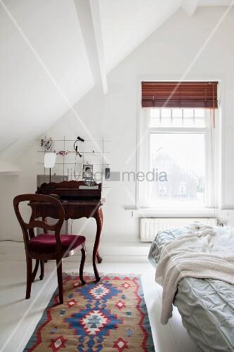 Antique bureau and chair in attic bedroom