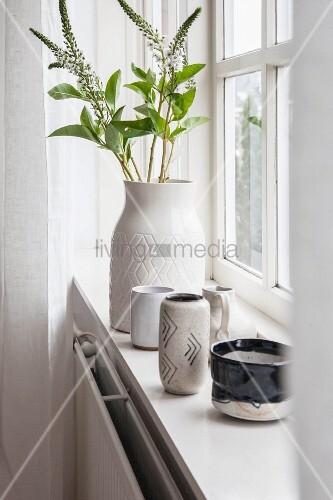 Vase of flowering twigs and various ceramic vessels on windowsill