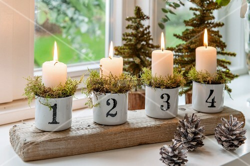 Lit pillar candles in vintage cups stuffed with moss, numbered and lined up on rustic wooden board