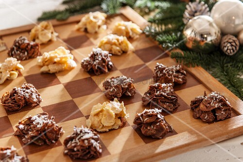 Light and dark cornflake cakes on chessboard next to Christmas decorations