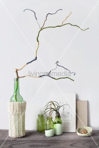 Decorative arrangement of branch covered in wool remnants of various colours, glass vase with knitted cover, three small bottles, air plant and books