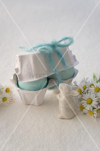 Hellblaue Ostereier im Eierkarton, Osterhase und Gänseblümchen