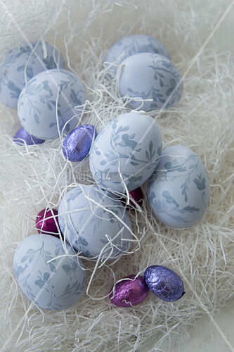 Painted Easter eggs and chocolate eggs amongst shredded paper
