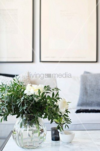White peonies and leaves in glass vase on marble table in front of sofa