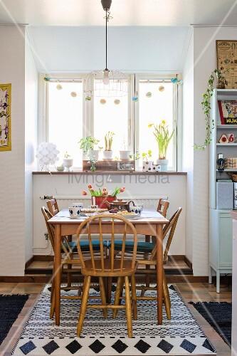 Wooden dining set below window