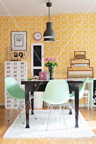 Pastellgrüne Schalenstühle um dunkelbrauen Holztisch in Esszimmer mit gelb-weiss gemusterter Tapete