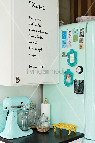 Mixer on kitchen cabinet next to mint-green retro fridge decorated with magnets