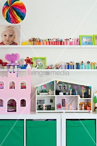 Puppenhaus und rosafarbenes Puppenschloss auf weißem Regalschrank mit grünen Aufbewahrungsboxen, darüber Spielzeugsammlung auf weißen Wandboards