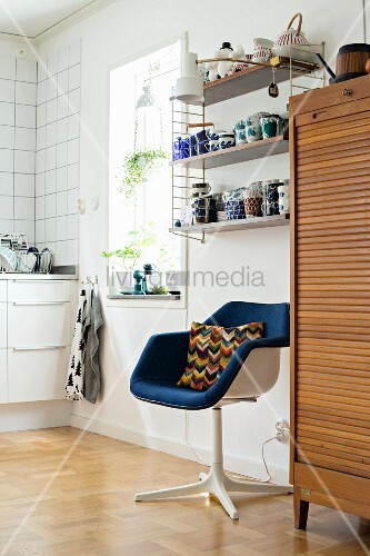 Retro swivel chair below crockery on String shelves next to wooden cabinet with roller door in kitchen area