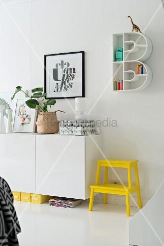 Knallgelber Tritthocker neben Sideboard, Regal in B-Form