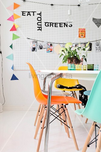 Table and colourful shell chairs in front of decorations hung on perforated wall panel