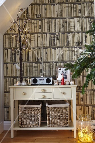 Cream-painted console table against photo mural with bookcase motif