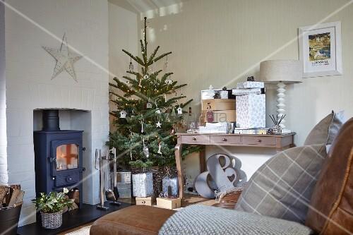Ländliches Wohnzimmer mit geschmücktem Weihnachtsbaum neben Kaminofen und Konsolentisch mit Geschenken