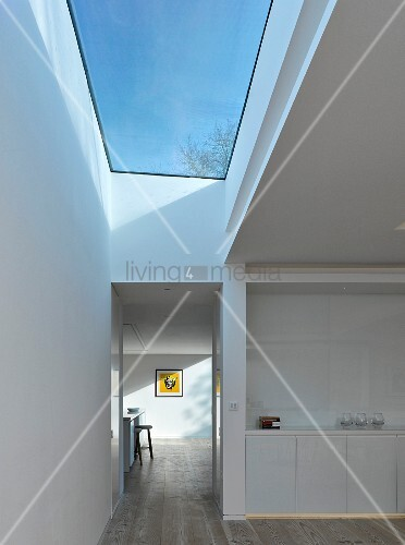 White kitchen counter and hallways with large skylight showing blue sky