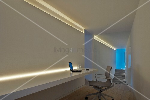 Modern office chair at long desk with indirect lighting in minimalist study with staircase in background