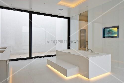 Designer bathtub with step and indirect lighting in minimalist, white, designer bathroom