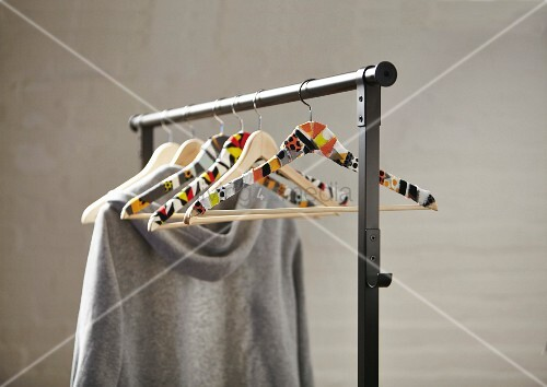 Coat hangers covered in fabric remnants on clothes rail