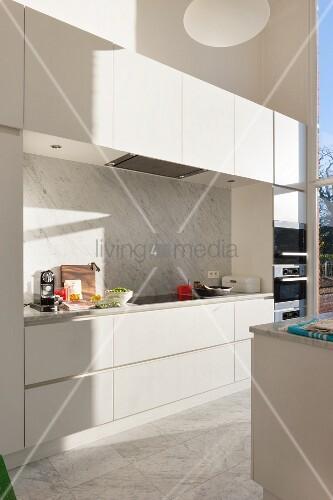 White modern kitchen with marble splashback and floor