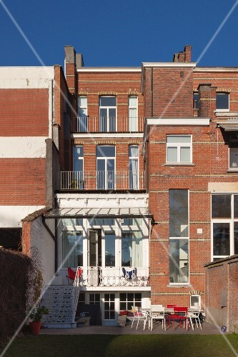 Four-storey brick town house with balcony outside raised ground floor and terrace in garden