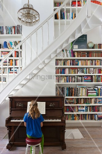 Girl playing piano at foot of staircase next to floor-to-ceiling bookcases