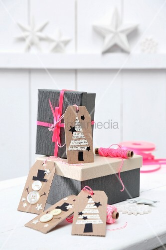Festive gift tags hand-made from brown cardboard on gift boxes