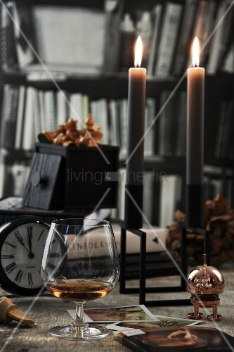 Brandy snifter next to lit candles and vintage-style clock