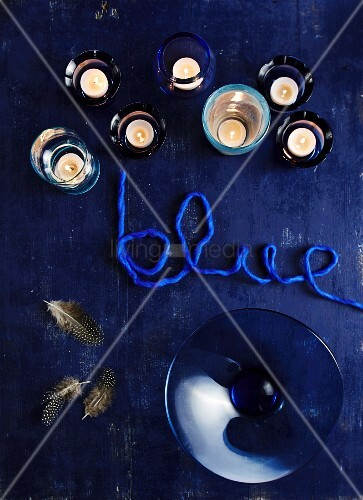 Tealight holders, glass dish and yarn lettering reading 'blue' on blue surface