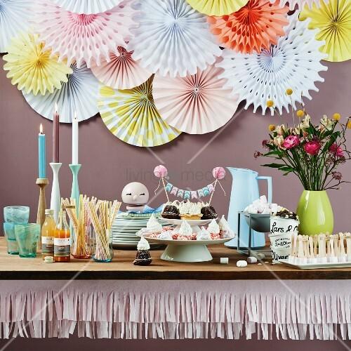 Partybuffet dekoriert mit Papiergirlande und Papierrosetten