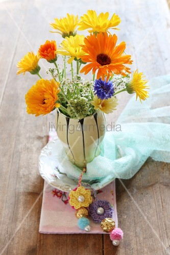 Vase of summer flowers decorated with crocheted flowers